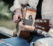 Man hands on the guitar strings close up image Royalty Free Stock Images