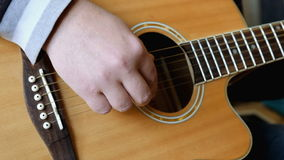 Man hands the guitar. The young man at home holding a guitar and play music stock video