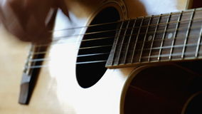 Man hands the guitar. The young man at home holding a guitar and play music stock video footage