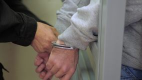 Man hands in handcuffs. Trial process with suspect in handcuffs. Man hands in handcuffs. Cop putting handcuffs on a suspect. Suspect on a trial. Evidence before stock footage