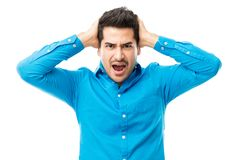 Man With Hands On Head Screaming Over White Background. Frustrated young man with hands on head screaming over white background stock photo