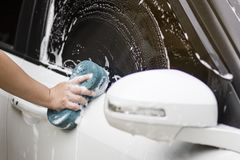 Man hands hold with blue sponge washing car. stock photos