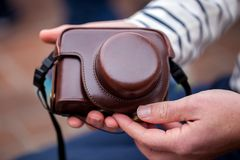 Man hands hold camera in an elegant and stylish leather case Royalty Free Stock Image