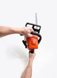 Man hands holding a chainsaw. On gray Stock Photo