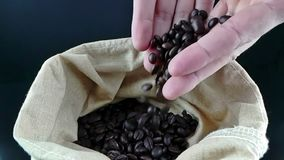 Man hands holding coffee beans in canvas sack and some falling down, shot slow motion, agriculture and nutrition stock video