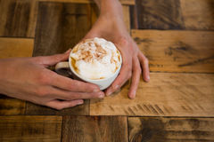 Man hands holding coffee cup at table in cafeteria Stock Photos