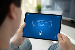 Man hands holding computer tablet with app personal assistant. On screen in the home room stock photo