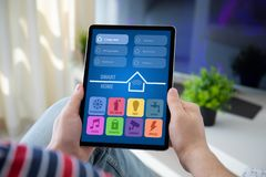 Man hands holding computer tablet with app smart home. On screen in the home room stock photos