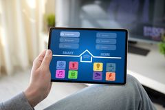 Man hands holding computer tablet with app smart home. On screen in the home room stock photo