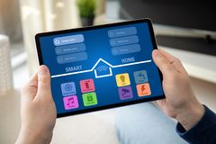 Man hands holding computer tablet with app smart home. On screen in the home room royalty free stock images