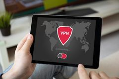 Man hands holding computer tablet with app vpn on screen. In the home room royalty free stock photos