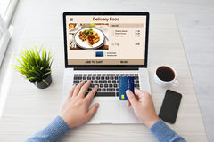 Man hands holding credit card and laptop with food delivery royalty free stock images