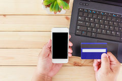 Man hands holding credit card and using smartphone for online shopping Royalty Free Stock Image