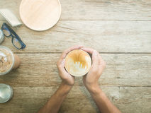 Man hands holding cups of coffee on wooden table background,Vint. Age Retro Filter Stock Photo