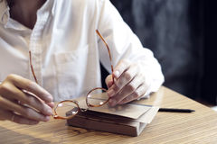Man hands holding an elegant eyeglasses with horn-rimmed, daylight in a cafe Stock Photo