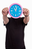 Man hands holding in front of his face a large wall clock showing time Royalty Free Stock Image