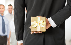Man hands holding gift box in office. Close up of men hands holding gift box in office Royalty Free Stock Photo