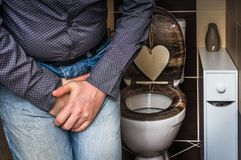 Man with hands holding his crotch - incontinence concept. Man with hands holding his crotch, he wants to pee in restroom - urinary incontinence concept Stock Images