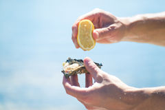Man hands holding lemon and oyster Stock Photos