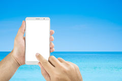 Man hands holding mobile phone isolated. Screens display on the beach background Stock Photography