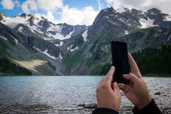 man hands holding mobile phone at Sea and mountains royalty free stock photos