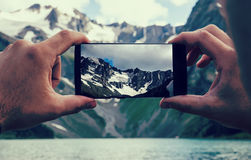 man hands holding mobile phone at Sea and mountains royalty free stock image