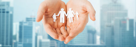 Man hands holding paper cutout of family Stock Photo