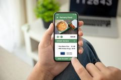 Man hands holding phone with app delivery food on screen. Man hands holding phone with app delivery food on the screen in the house in room stock photos