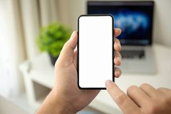 Man hands holding phone with isolated screen in the room. Man hands holding phone with isolated screen in the house in room stock photos