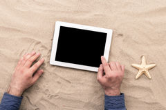 Man hands holding tablet with blank screen on the beach stock images