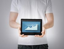 Man hands holding tablet pc with graph Stock Images