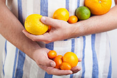 Man hands holding various citrus fruits Royalty Free Stock Photography