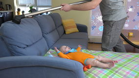 Man hands hoover dust from sofa around baby daughter. 4K stock video footage