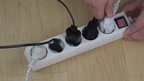 Man hands insert wire plugs and turn on extension switch on wooden floor. Man hands insert wire plugs and turn on extension switch on wooden floor at home stock video footage