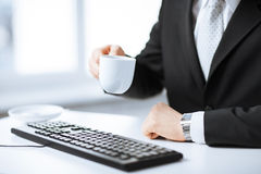 Man hands with keyboard drinking coffee Royalty Free Stock Image