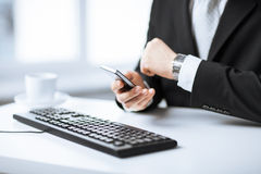 Man hands with keyboard, smartphone and wristwatch Stock Photo