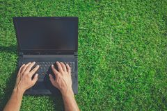 Man hands on laptop keyboard on the grass. Business, technology. High angle view of man using blank screen laptop on grass. Technology and green energy concepts Royalty Free Stock Photography