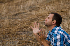 Man with hands lifted in worship and praise. Man praying outside on a hill with his spread out in worship Royalty Free Stock Photos