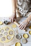 Man hands making shortcrust pastry for little tart on molds on rustic background with rolling pin and flour Stock Photography