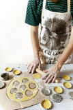 Man hands making shortcrust pastry for little tart on molds on rustic background with rolling pin and flour Stock Photos