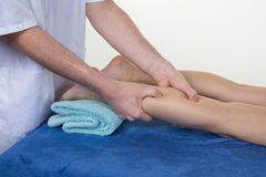 Man Hands massaging woman calf muscle.Therapist applying pressure on leg. Stock Image