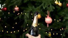Man hands open bottle of champagne on decorated Christmas tree background, New Year celebration concept. Man hands stock photos
