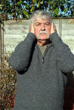 Stopping noise.Man with hands over his ears. An elderly man with his hands covering his ears so that he can not hear and stop the noise stock image