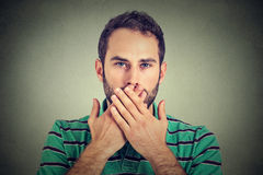 Man with hands over his mouth, speechless isolated on gray wall background Stock Image