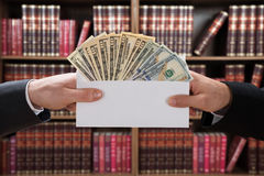 Man Hands Passing Bribe In Envelope. Cropped image of man's hands passing bribe to judge in envelope at courtroom royalty free stock photography