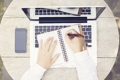Man hands with pen, diary and blank black cell phone on wooden t Royalty Free Stock Photo