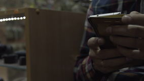 The man in the hands of the phone. The guy sitting on a chair holding a smartphone stock footage