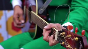 Man in green colour suit playing the black acoustic guitar. Man hands playing the acoustic guitar. Adult man in green colour suit playing the black acoustic stock video footage