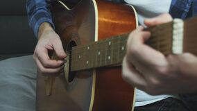 Man hands playing on acoustic guitar. Fingers strumming on acoustic guitar strings. Close up