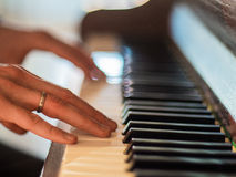 Man hands playing the piano. Close up.  Stock Photography
